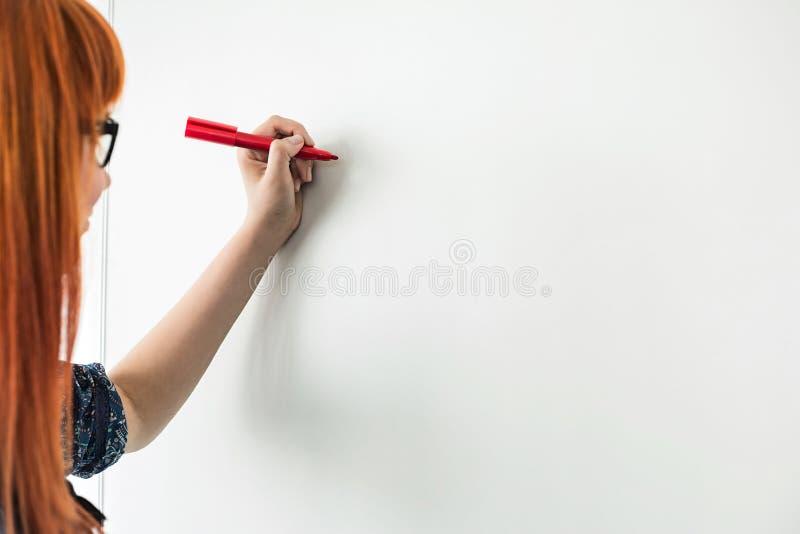 Imagen cosechada de las empresarias que escriben en whiteboard en oficina creativa fotos de archivo libres de regalías
