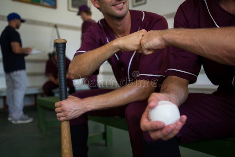 Imagen cosechada de los jugadores de béisbol que se sientan en banco fotos de archivo