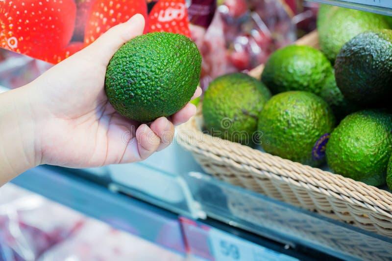 Imagen cosechada de un cliente que elige los aguacates en el supermercado Ciérrese para arriba de la mano de la mujer que sostien imagen de archivo