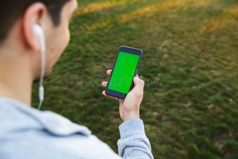 Imagen cosechada de un deportista joven hermoso que usa el teléfono móvil foto de archivo