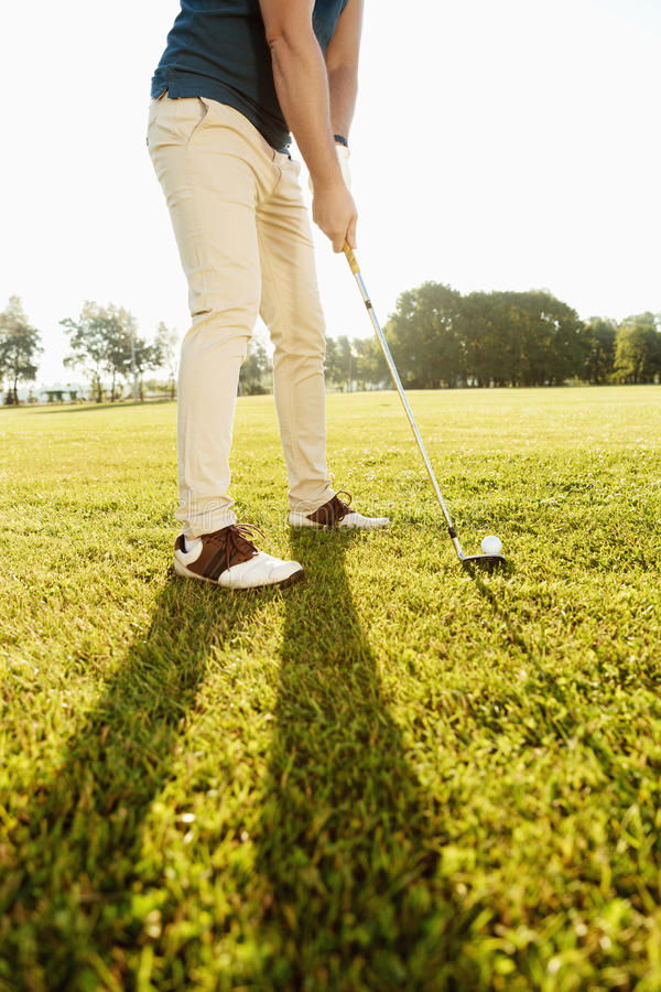 Imagen cosechada de un golfista que pone la pelota de golf en verde imagen de archivo libre de regalías