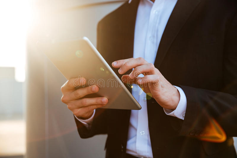 Imagen cosechada de un hombre de negocios acertado que sostiene la tableta de la PC al aire libre fotos de archivo libres de regalías