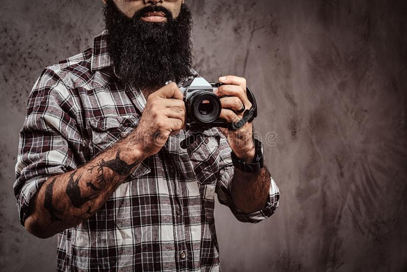 Imagen cosechada de un varón barbudo tatuado que lleva una camisa a cuadros que sostiene una cámara imágenes de archivo libres de regalías