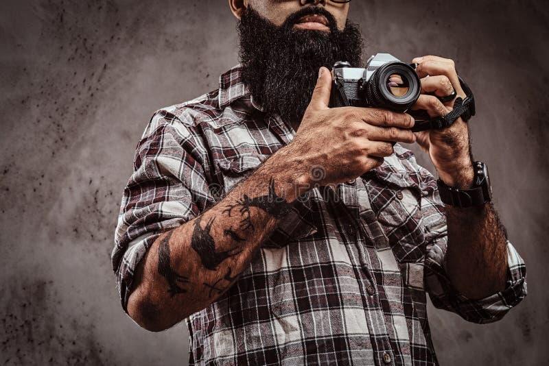 Imagen cosechada de un varón barbudo tatuado que lleva una camisa a cuadros que sostiene una cámara imagenes de archivo