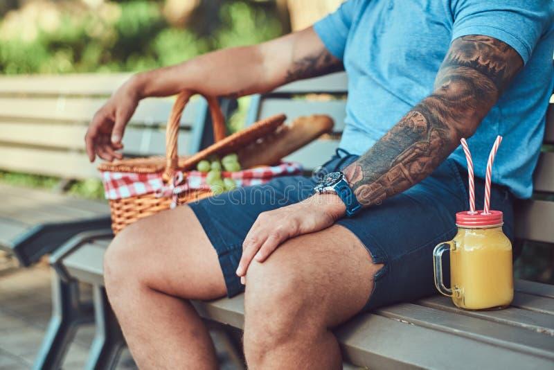 Imagen cosechada de una camisa que lleva masculina tatuada y de los pantalones cortos que se sientan con una cesta de la comida c fotografía de archivo libre de regalías