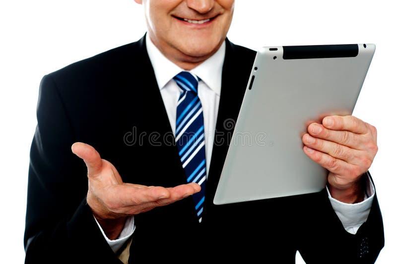 Imagen cosechada de una PC de la tablilla de la explotación agrícola del hombre de negocios imagen de archivo