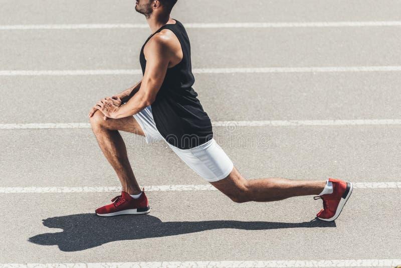 imagen cosechada del basculador masculino que estira en pista de funcionamiento en el deporte foto de archivo libre de regalías