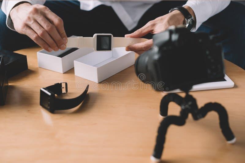 imagen cosechada del blogger de la tecnología que celebra el nuevo reloj elegante en frente foto de archivo