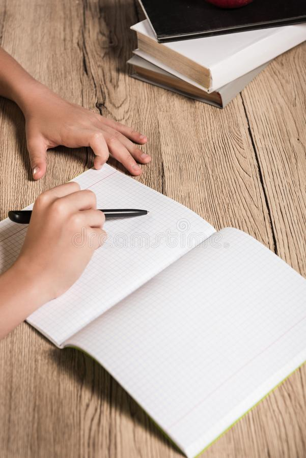 imagen cosechada del colegial que hace la preparación en libro de texto vacío en la tabla con la pila foto de archivo libre de regalías