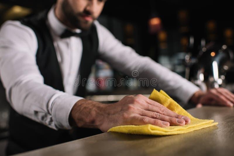 imagen cosechada del contador de la barra de la limpieza del camarero fotos de archivo libres de regalías