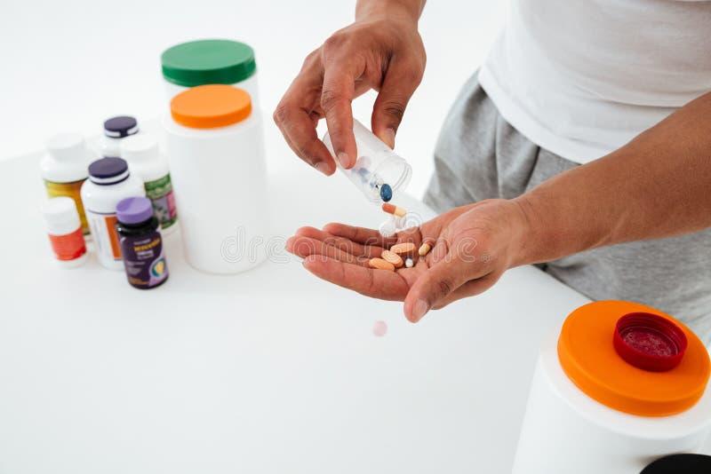 Imagen cosechada del deportista joven que sostiene las vitaminas y las píldoras del deporte imagen de archivo
