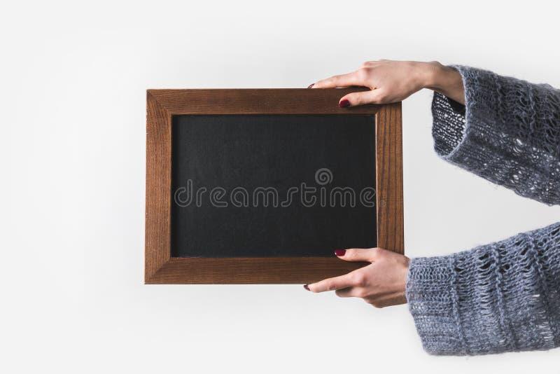 imagen cosechada del hombre que lleva a cabo al tablero negro vacío aislado en blanco fotografía de archivo libre de regalías