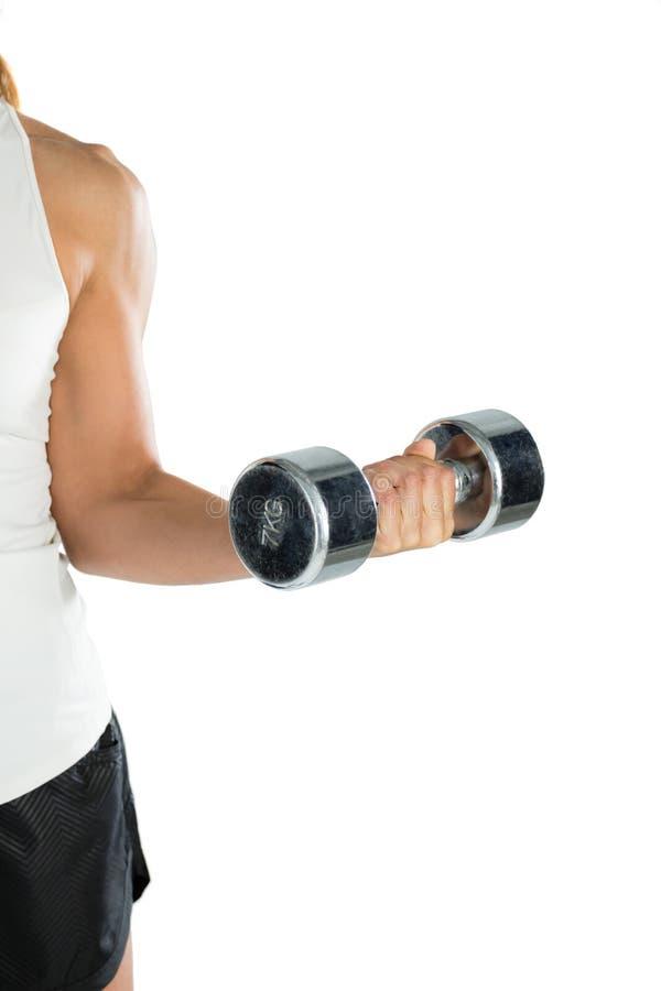 Imagen cosechada del jugador femenino que ejercita con pesa de gimnasia foto de archivo libre de regalías