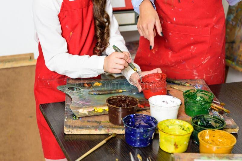 imagen cosechada del profesor y del alumno que toman las pinturas de cartel en taller de foto de archivo