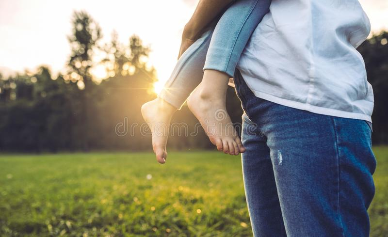 Imagen cosechada horizontal de la mujer hermosa abrazar a su muchacha al aire libre Madre e hija de amor que presentan en el parq fotografía de archivo