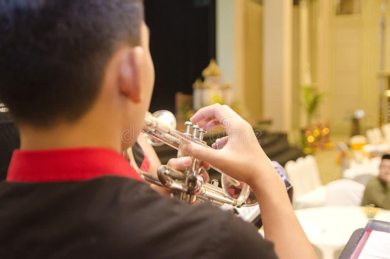 Imagen cosechada y del backview, muchacho que toca la trompeta con un orchestr fotografía de archivo libre de regalías
