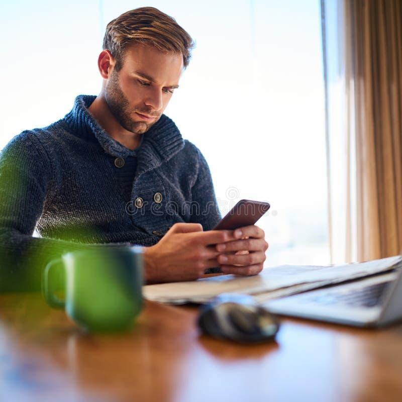 Imagen cuadrada del hombre joven que manda un SMS en su teléfono móvil imagen de archivo