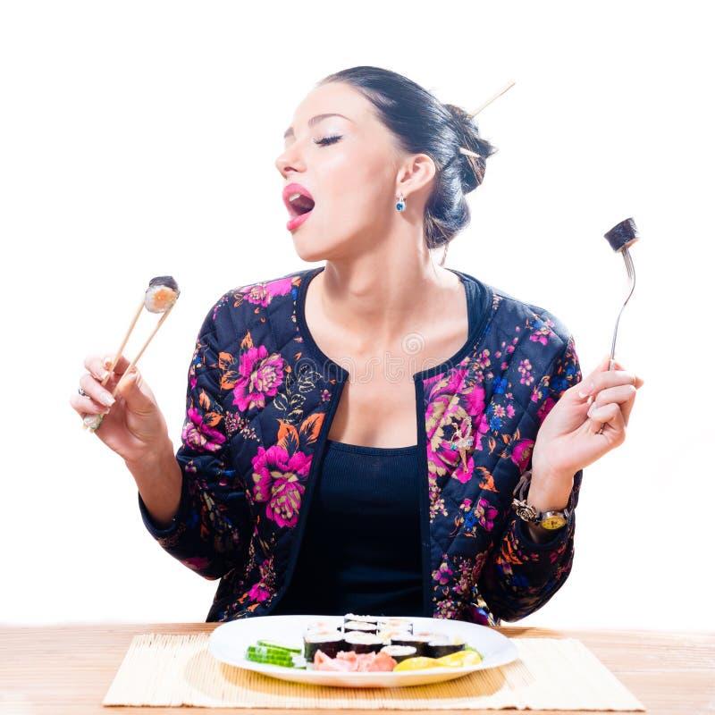Imagen de aislado en la mujer morena atractiva hermosa del fondo blanco que come el sushi con los palillos y la bifurcación foto de archivo