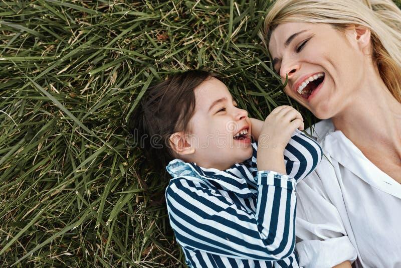 Imagen de arriba del primer de la mujer hermosa feliz que ríe y que juega con su niña linda que miente en hierba verde en el parq imágenes de archivo libres de regalías
