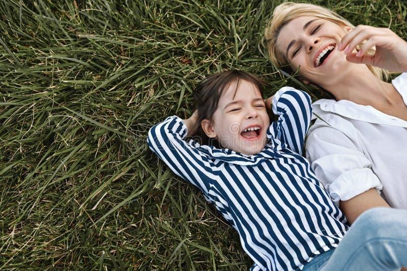 Imagen de arriba horizontal de la mujer hermosa feliz que ríe y que juega con su niña linda que miente en hierba verde en el parq fotos de archivo libres de regalías
