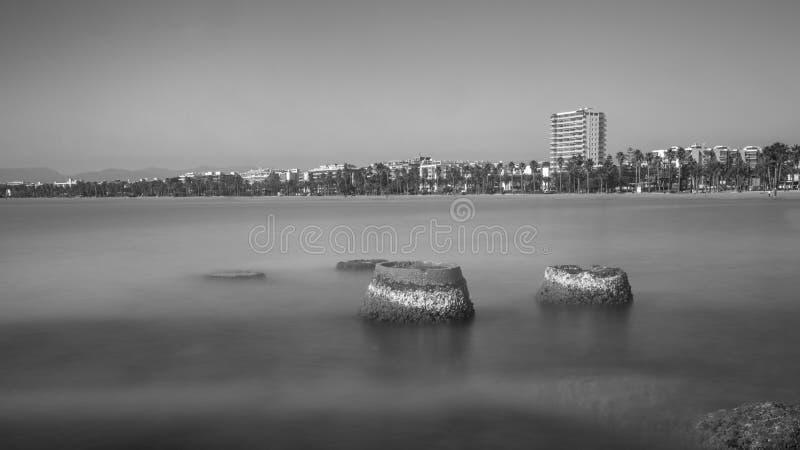 Imagen de B/W de la playa principal de Salou; dos bases de los pilars del ciment paradas más imagen de archivo