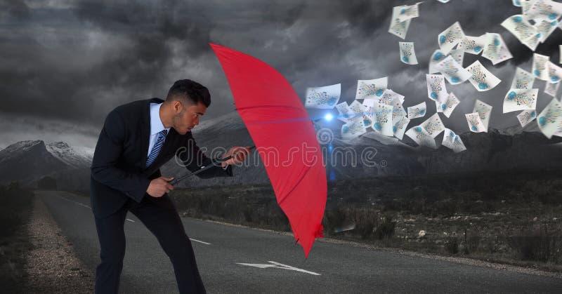 Imagen de Digitaces de los documentos defencing del hombre de negocios con el paraguas rojo mientras que se opone en el camino al fotografía de archivo
