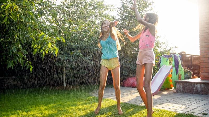 Imagen de dos adolescentes de risa felices que saltan y que bailan debajo de la lluvia caliente del verano en el jard?n del patio imágenes de archivo libres de regalías