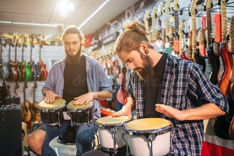 Imagen de dos hombres jovenes que sientan y que tienen golpe en los tambores Están en el sitio lleno de guitarras eléctricas Los  imagen de archivo libre de regalías