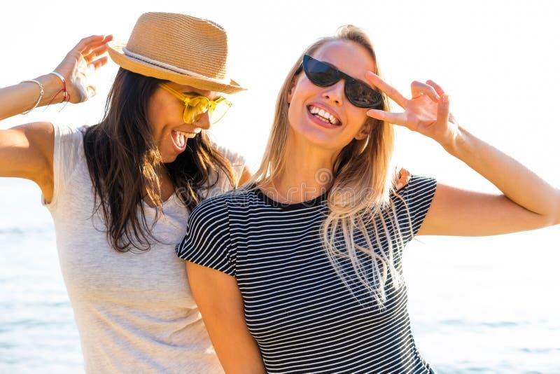 Imagen de dos muchachas multiétnicas 20s en la ropa elegante que ríe y que disfruta de verano durante partido de la playa en la p foto de archivo