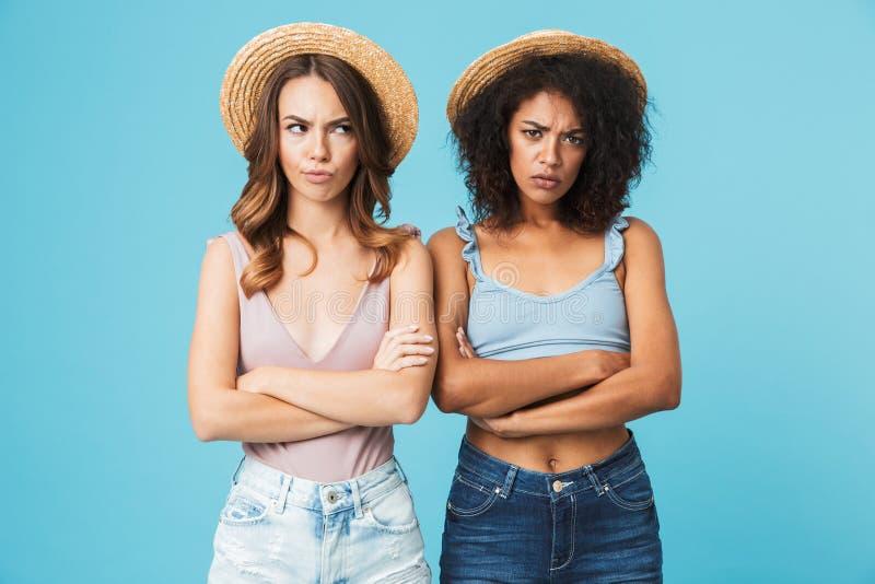 Imagen de dos mujeres negativas con diverso color de la piel en stra fotografía de archivo