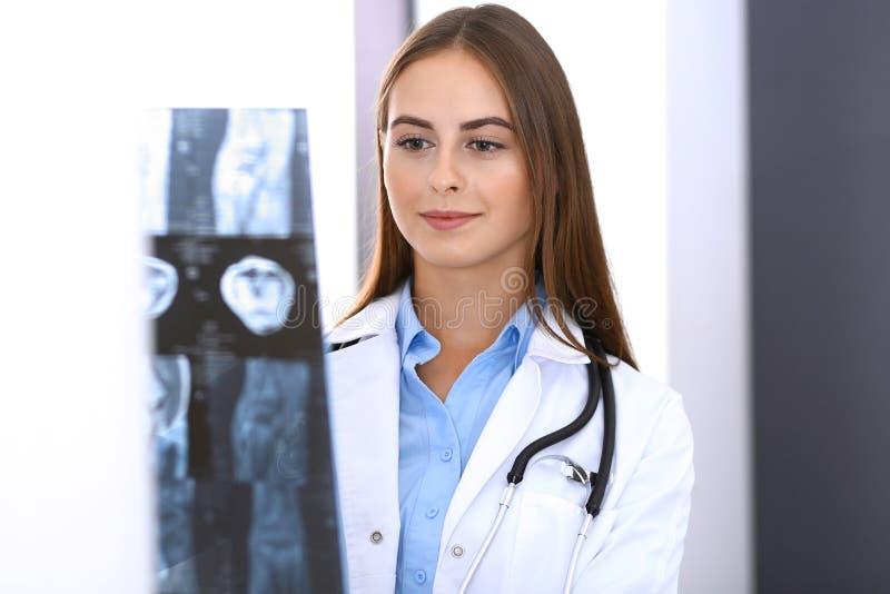 Imagen de examen de la radiografía de la mujer del doctor mientras que coloca la ventana cercana en hospital Cirujano u ortopedis fotografía de archivo libre de regalías