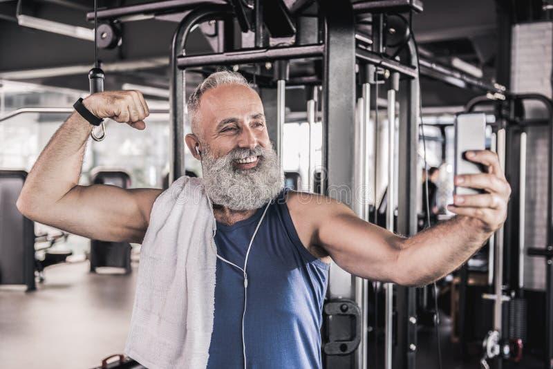 Imagen de fabricación masculina mayor alegre de sí mismo en gimnasio moderno imagen de archivo libre de regalías