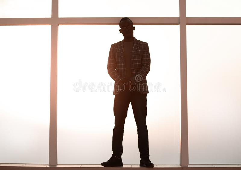 Imagen de fondo hombre de negocios que se coloca cerca de la ventana fotografía de archivo libre de regalías