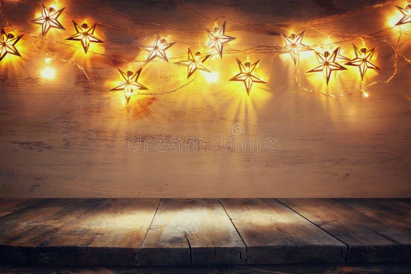 Imagen de fondo de la mesa de madera frente a las cálidas luces de guirnaldas de oro de Navidad filtrado enfoque selectivo imagen de archivo libre de regalías