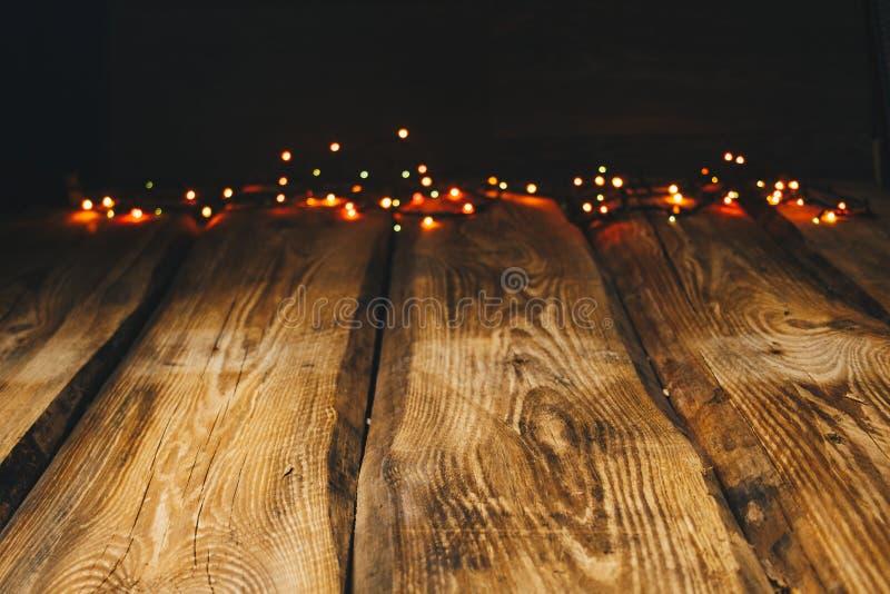 Imagen de fondo papeles pintados en la mesa en el estilo del Año Nuevo Fondo de madera de la foto con las guirnaldas y bokeh en n fotos de archivo