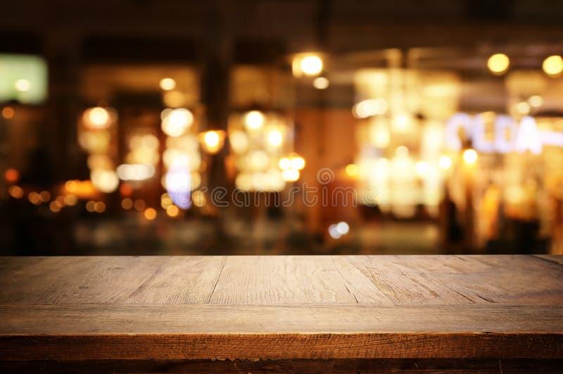 Imagen de fondo de una mesa de madera frente a abstractas luces borrosas en los restaurantes imagen de archivo libre de regalías