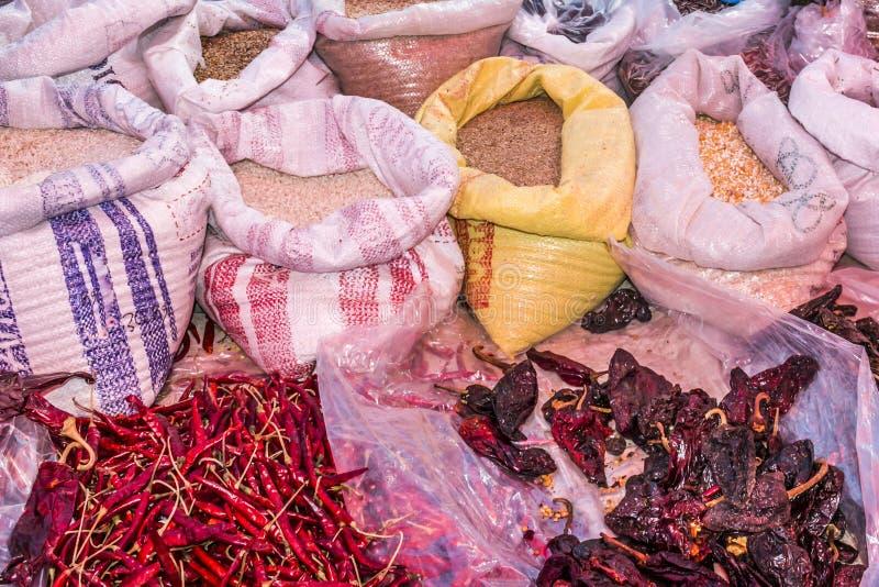 Imagen de granos en sacos y pimientas de chile y chile secos rojos del pasilla en un mercado mexicano fotografía de archivo libre de regalías