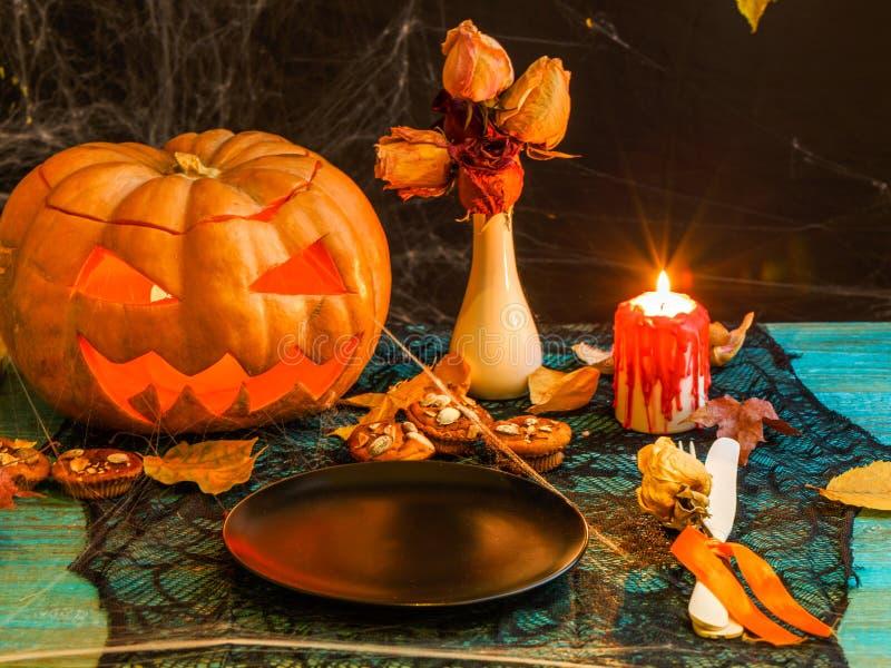 Imagen de Halloween de la tabla con la calabaza, vela ardiente, imagen de archivo