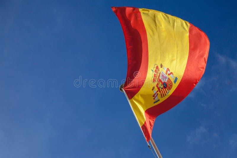 Imagen de la bandera española que renuncia en el aire en una tarde soleada con un fondo del cielo azul imagen de archivo