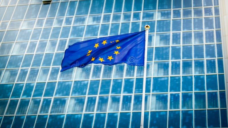 Imagen de la bandera de unión europea con staras sobre fondo azul contra el edificio de oficinas moderno grande Concepto de eceno imagen de archivo libre de regalías