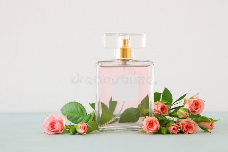 Imagen de la botella de perfume con las flores de los pétalos color de rosa sobre la tabla en colores pastel Concepto floral del  foto de archivo libre de regalías