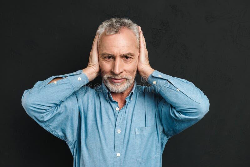 Imagen de la camisa que lleva irritada del hombre 50s que ase su cabeza y c fotos de archivo