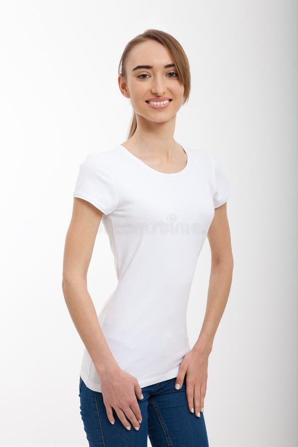 Imagen de la camiseta blanca que lleva sonriente de la chica joven con el lugar para el texto y tejanos, espacio de la copia y mo fotos de archivo