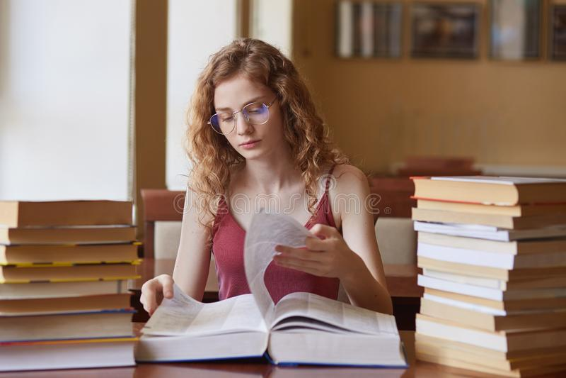 Imagen de la chica joven de trabajo dura pensativa que vuelca las páginas del libro enorme, buscando para la información apropiad fotos de archivo libres de regalías