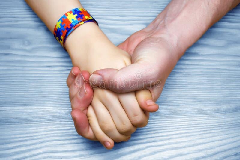 Imagen de la conciencia del autismo Mano de la tenencia del padre su niño autístico fotografía de archivo