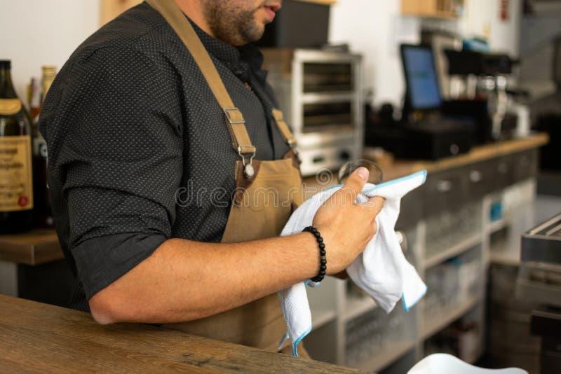 Imagen de la copa de vino de limpieza del camarero en un pub imagen de archivo