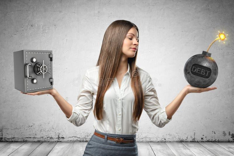 Imagen de la cosecha de la empresaria hermosa joven que sostiene poca caja fuerte del dinero en una bomba de la mano y de la bola fotos de archivo libres de regalías