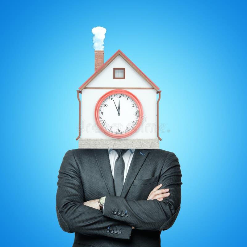 Imagen de la cosecha de un hombre de negocios con los brazos doblados y de una casa con una chimenea que fuma y de una reloj-cara fotografía de archivo