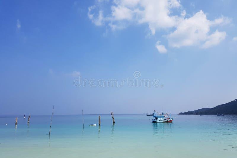 Imagen de la costa de mar con las colinas, el barco y el cielo nublado foto de archivo
