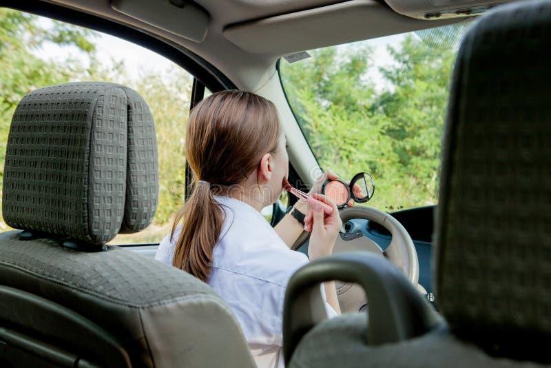 Imagen de la empresaria joven que hace maquillaje mientras que conduce un coche en el atasco fotografía de archivo libre de regalías